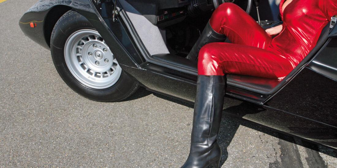 Blondine im roten Catsuit steigt aus Lamborghini Countach aus