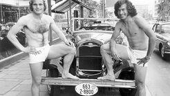 Paul Breitner und Uli Honeß in Badehosen vor Ford